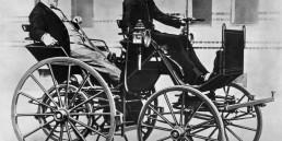 """Im Jahr 1886 baut Gottlieb Daimler mit der """"Motorkutsche"""" sein erstes vierrädriges Automobil. Das Foto zeigt ihn im Fahrzeug, chauffiert von seinem Sohn Adolf."""
