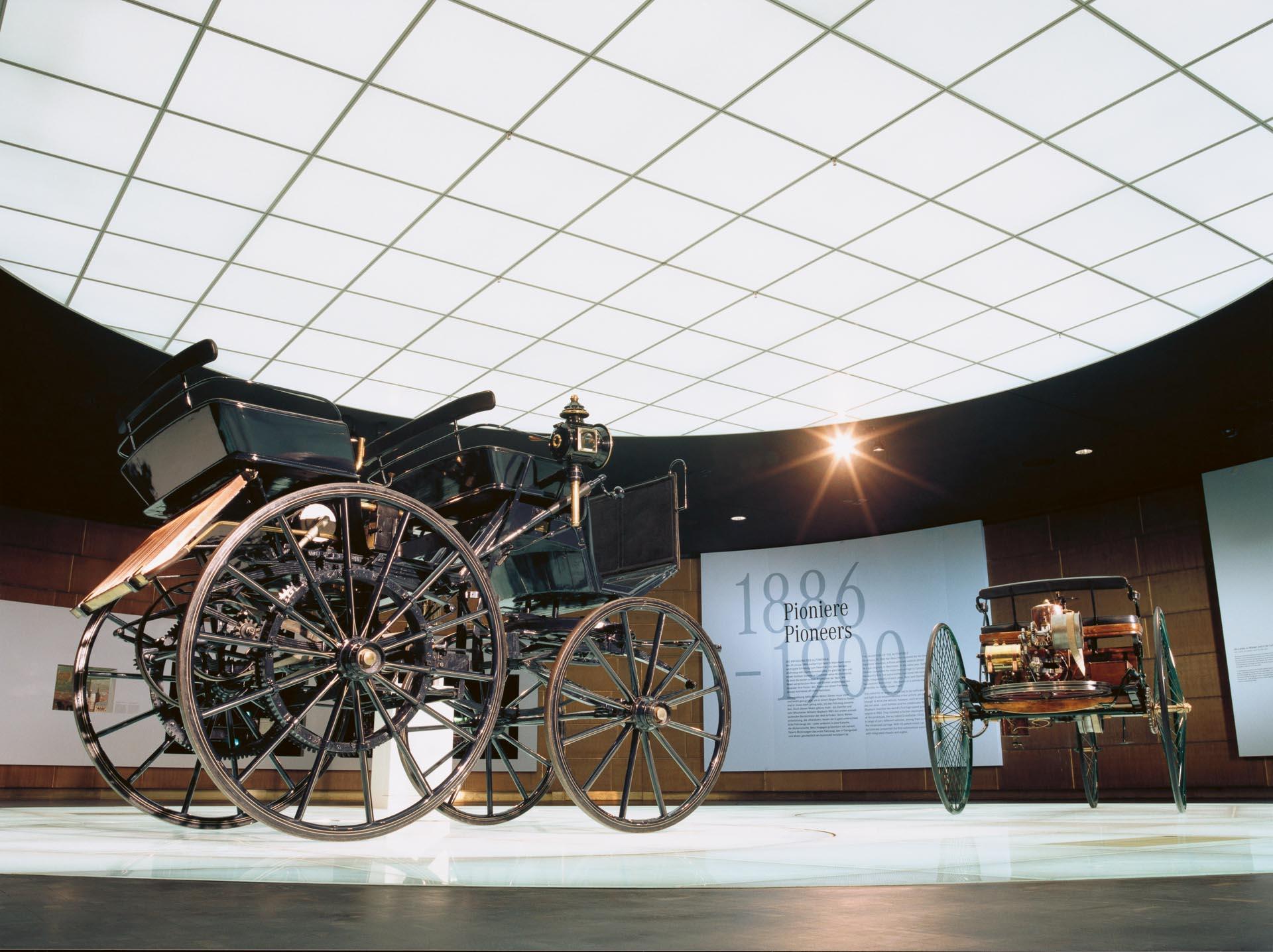 """Mercedes-Benz Museum, Mythosraum 1 """"Pioniere – Die Erfindung des Automobils"""" mit der Motorkutsche von Gottlieb Daimler (Vordergrund) und dem Patent-Motorwagen von Carl Benz als Zentralexponate."""