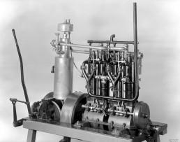 Erster Vierzylinder-Benzinmotor, ein Bootsmotor. Das erste Exemplar liefert die Daimler-Motoren-Gesellschaft am 21. August 1890 nach New York aus. Konstruiert hat ihn Wilhelm Maybach. Zu den technischen Details gehören unter anderem eine dreifach gelagerte und vierfach gekröpfte Kurbelwelle, die Ventilsteuerung über eine Nockenwelle, hängende Auslassventile sowie eine effektive Zylinderkühlung über Wassermäntel. First four-cylinder petrol engine, a marine engine. Daimler-Motoren-Gesellschaft delivered the first of these cars to New York on 21 August 1890. It had been designed by Wilhelm Maybach. The technical refinements included a three-bearing, four-throw crankshaft, valve train via a camshaft, overhead exhaust valves and effective cylinder cooling using water jackets.