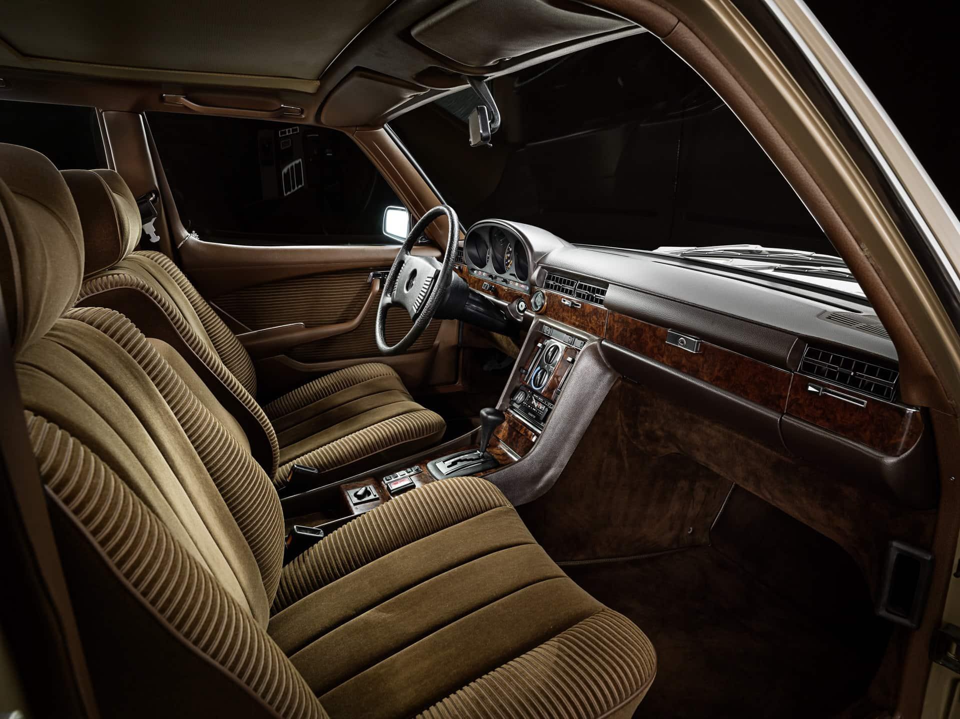 Mercedes-Benz S-Klasse, Limousine der Baureihe 116 (1972 bis 1980), Interieur mit Instrumententafel. Der Zuwachs an Fahrzeugsystemen für mehr Sicherheit und Komfort erfordert auch neue ergonomische Lösungen: Erstmals befindet sich unterhalb der Instrumententafel eine Konsole mit den Schiebeschaltern und Reglern für Heizung und Belüftung sowie für das Autoradio. Foto eines 450 SEL 6.9, Baujahr 1980, aufgenommen im Jahr 2005. Mercedes-Benz model series 116 S-Class Saloon (1972 to 1980), interior with instrument panel. The increase in onboard systems for greater safety and comfort also required new ergonomic solutions: for the first time, a console was installed beneath the dashboard to house the slide switches and controls for the heating and ventilation, as well as the radio. Image of a 450 SEL 6.9, produced in 1980, taken in 2005.