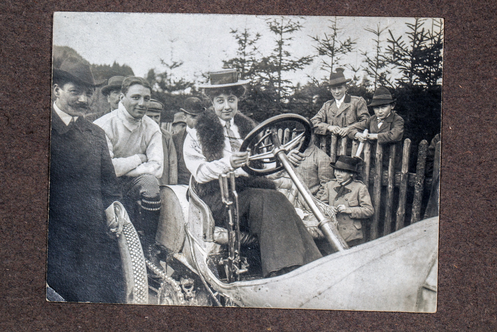 Mercédès Jellinek auf einem Mercedes Rennwagen, aufgenommen um 1906. Das Foto ist Teil eines Konvoluts mit zahlreichen Fotografien sowie Originaldokumenten aus dem Nachlass von Mercédès Jellinek, das seit 2012 zum Bestand der Archive von Mercedes-Benz Classic gehört. Mercédès Jellinek in a Mercedes racing car, photographed around 1906. The photo is part of a bundle of other original documents and numerous photographs from the estate of Mercédès Jellinek, which is part of the Mercedes-Benz Classic archives since 2012.