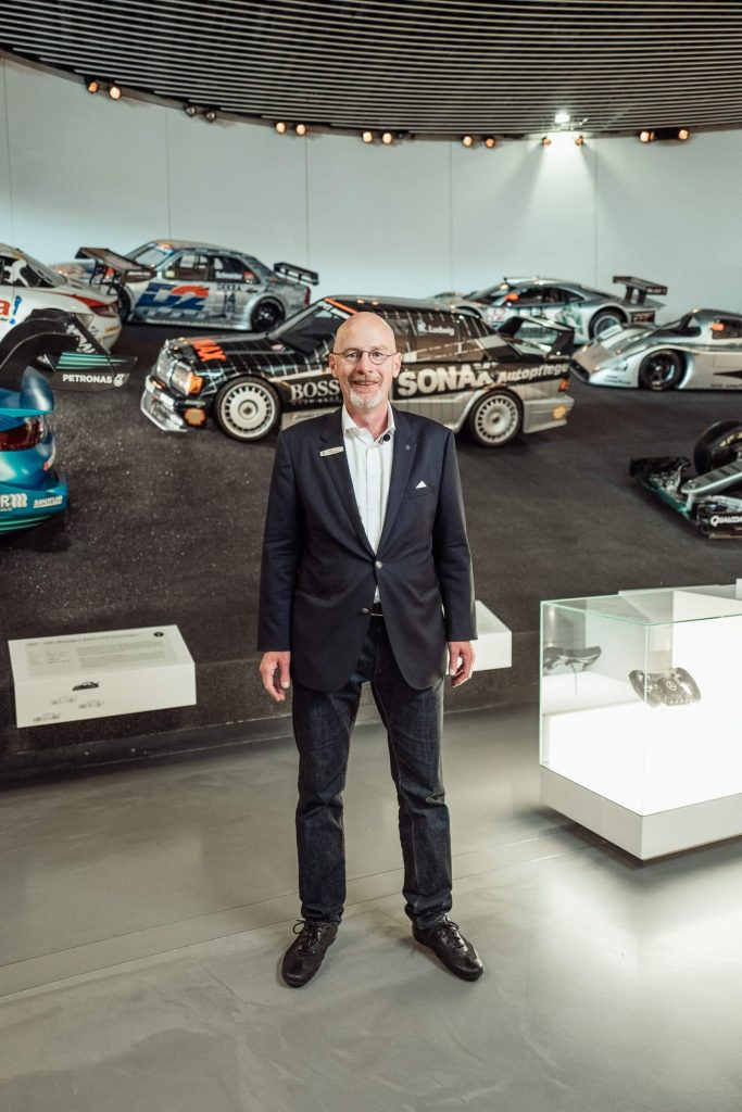 """Dreharbeiten für die sechste Folge der Videoserie """"Exclusive Insights: The Cars of the Mercedes-Benz Museum"""" auf Instagram TV. Museumsguide Pádraic Ó Leanacháin vor dem Mercedes-Benz 300 TD im Collectionsraum 1: Galerie der Reisen."""