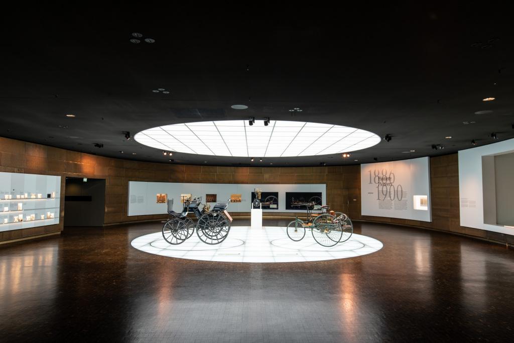 Mythos 1: Pioniere – Die Erfindung des Automobils,1886 bis 1900 / Mercedes-Benz Museum. Wer von den spektakulärsten Errungenschaften der vergangenen Jahrhunderte berichtet, wird immer wieder bei jenem technischen Gerät landen, das die Welt entscheidend verändert hat – dem Automobil. Seine Erfinder sind Gottlieb Daimler und Carl Benz. Sie bringen unabhängig voneinander 1886 die ersten Automobile ins Rollen. Mit ihren genialen Erfindungen und der Unterstützung ebenso genialer und tatkräftiger Partner – bei Daimler ist es der Ingenieur Wilhelm Maybach, bei Benz dessen Ehefrau Bertha - machen sie die Welt erst so richtig mobil. Ihre Antriebsfeder? Eine hochexplosive Mischung aus Neugier, Forscherdrang und einem siebten Sinn für das technisch Machbare, die sich immer wieder in spektakulären Entwicklungen entlädt und den bis dato unerfüllten Traum der individuellen Mobilität Wirklichkeit werden lässt.