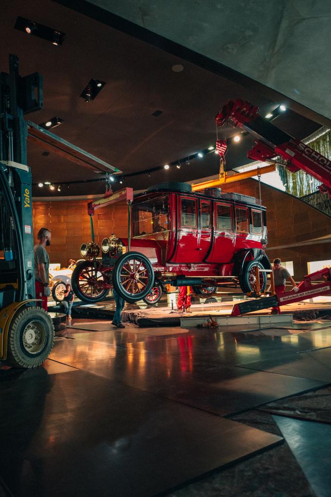 Ausbringung der Mercedes-Simplex 60 PS Reiselimousine von Emil Jellinek aus dem Mercedes-Benz Museum, August 2020. Nach mehrstündiger Vorbereitung geht es an den eigentlichen Hub. Dabei schwebt das Fahrzeug, von Minikran und Stapler getragen, vorsichtig von seinem Standplatz auf den Museumsboden.