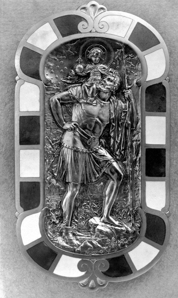 Plakette im Mercedes-Benz Nürburg Papstwagen aus dem Jahr 1930: Sankt Christophorus mit Wanderstab trägt das Christuskind auf seiner Schulter über einen Fluss. Die Plakette des Schutzpatrons der Autofahrer ist rechts an der Seitenwand des Fahrzeugs direkt neben dem Sessel des Heiligen Vaters angebracht. (Fotosignatur der Mercedes-Benz Archive: 1993M1051)