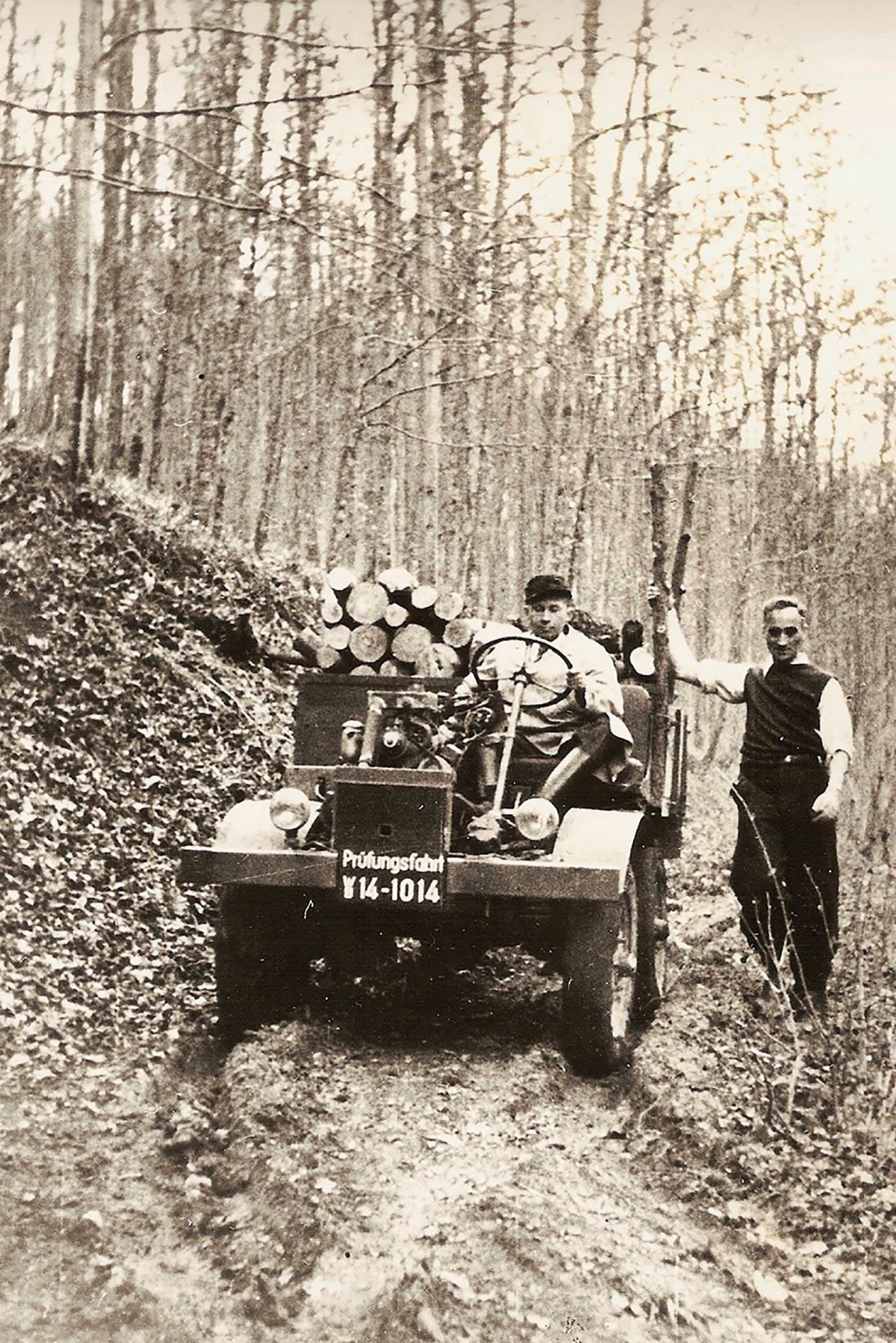 """Erste """"Prüffahrt"""", noch ohne Fahrerhaus, am 9. Oktober 1946. Chefkonstrukteur Heinrich Rößler am Steuer, rechts Hans Zabel, der Namensgeber des Unimog"""