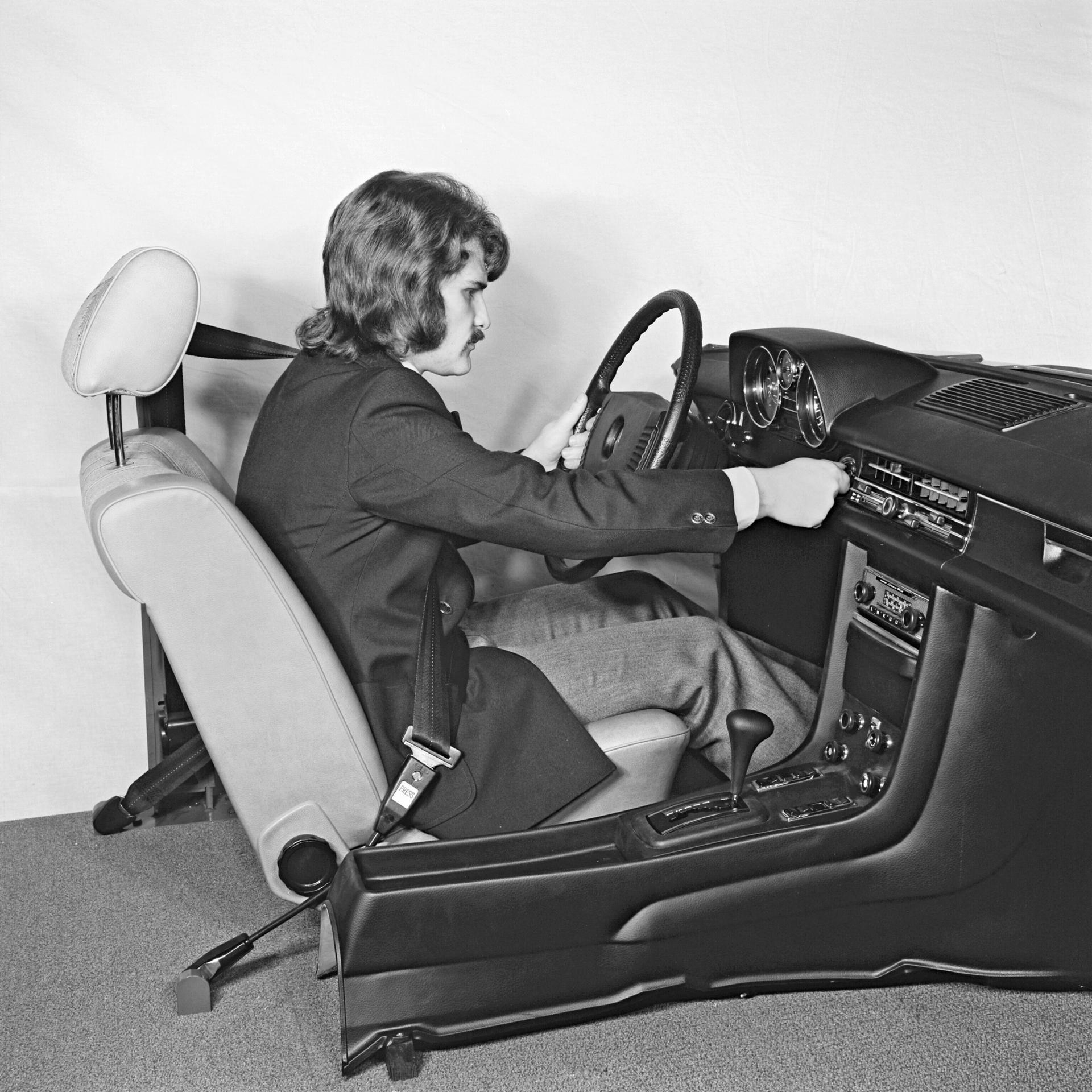 """Die Sicherheitsforschung der damaligen Daimler-Benz AG untersucht mit dieser Versuchsanordnung zur Ergonomie, wie sich in den """"Strich-Acht""""-Limousinen der Baureihen 115 und 114 (1968 bis 1976) bei angelegtem Dreipunktautomatikgurt Lenkrad und Armaturenanlage bedienen lassen."""
