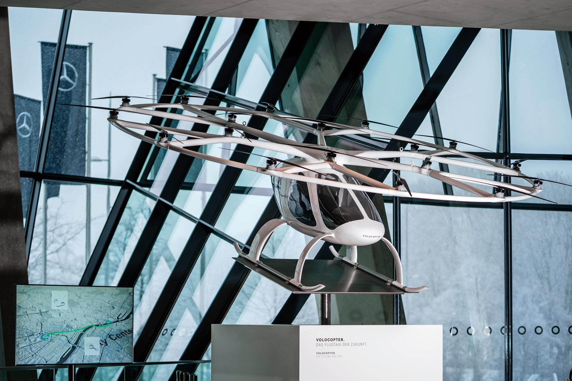 """Mercedes-Benz Museum, Sonderausstellung """"Zukunft Mobilität"""" vom 1. Juni 2021 bis Ende März 2022. Vollelektrisches Flugtaxi VoloCity mit 18 Rotoren von Volocopter. Schon in den nächsten Jahren soll es kommerzielle Passagierflüge ohne lokale Emissionen und Lärm geben. Im September 2019 ist ein Volocopter vom Mercedes-Benz Museum aus zum ersten Flug in einem europäischen Stadtgebiet gestartet."""