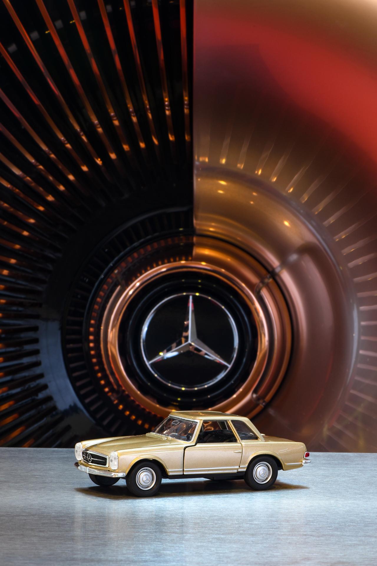 """Mercedes-Benz 230 SL """"Pagode"""" (W 113) in Sandbeigemetallic. Modellauto im Maßstab 1:24 aus Zinkdruckguss mit Kunststoffteilen aus dem Programm des Mercedes-Benz Classic Shops. Preis 29,90 Euro. Inszeniertes Foto in der Dauerausstellung des Mercedes-Benz Museums."""