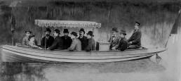 """Im August 1886 unternehmen Gottlieb Daimler und Wilhelm Maybach erste Probefahrten mit Daimler-Motorbooten auf dem Neckar bei Cannstatt. Das Foto zeigt Daimler und Maybach (3. und 2. von rechts) direkt am Motorgehäuse der """"Neckar"""" sitzend."""