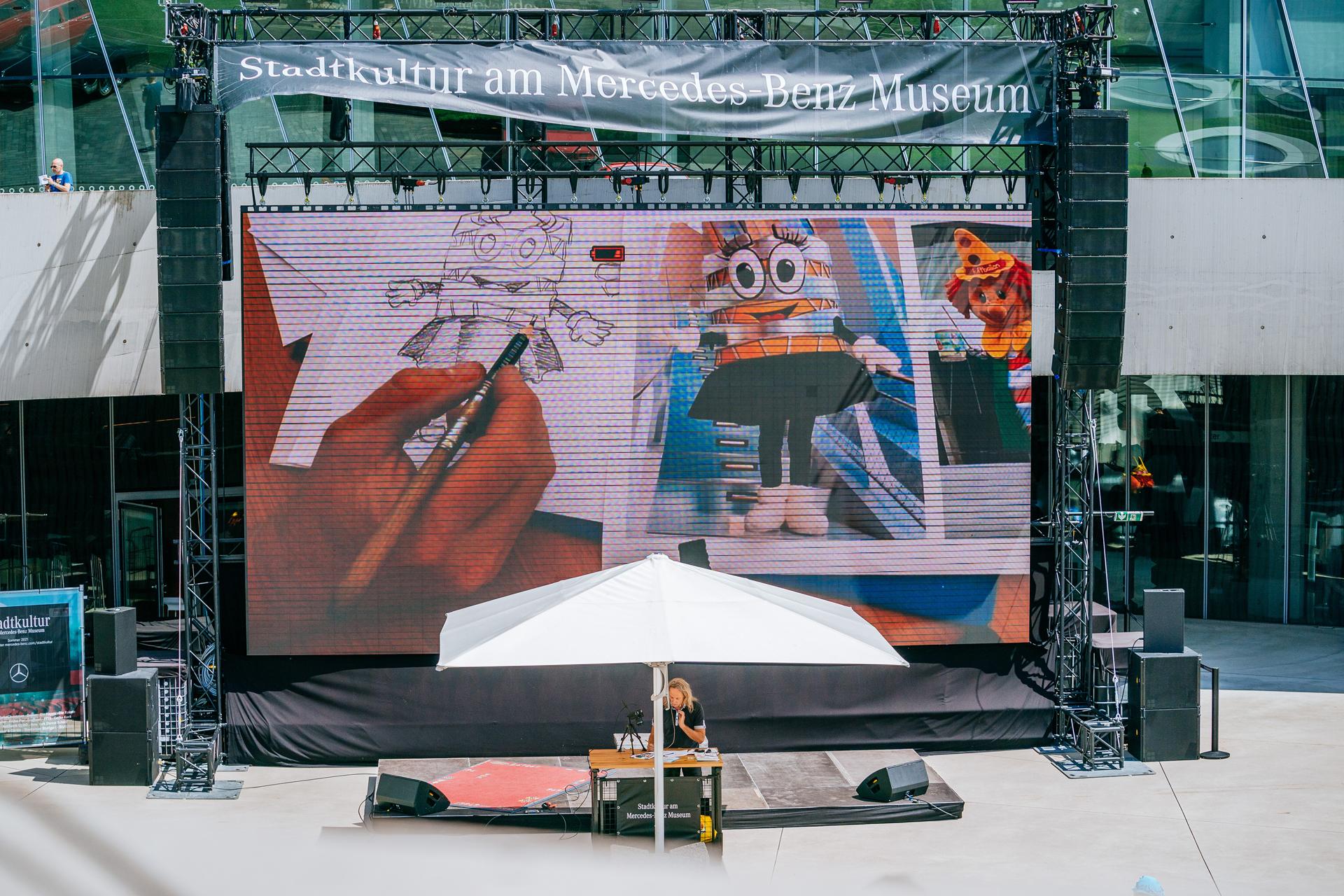 """""""Stadtkultur am Mercedes-Benz Museum"""", Kinderzeichenkurs am 18. Juli 2021 mit Gecko Keck sowie den Maskottchen Luftikus und Carlotta auf der Open Air Bühne am Museum."""
