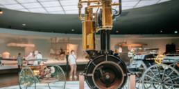 """Mercedes-Benz Museum, Raum Mythos 1: Pioniere – die Erfindung des Automobils. Schnell laufender Einzylinder-Viertaktmotor von Gottlieb Daimler, wegen des charakteristischen Aussehens """"Standuhr"""" genannt. Erstmals wird der Motor in dieser Bauform 1884 verwirklicht. 1885 erfolgt der erste Einsatz im """"Reitwagen"""", 1886 dann in der """"Motorkutsche"""", dem ersten vierrädrigen Automobil der Welt."""